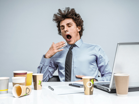 manage clutter: Sleepy exhausted young manager in yawn. Modern businessman at the workplace working with computer, depression and crisis concept