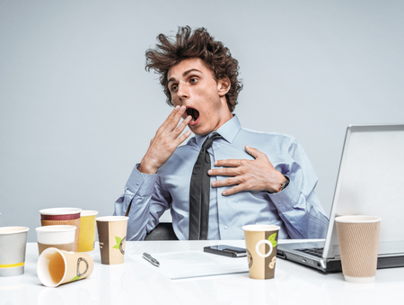 manage clutter: Sleepy exhausted or bored young businessman in yawn. An exhausted or bored manager yawning with his hand to his wide open mouth and apathetic eyes Stock Photo