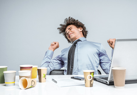 manage clutter: Student stretches from fatigue, kneads the back at the workplace. Long working hours Stock Photo