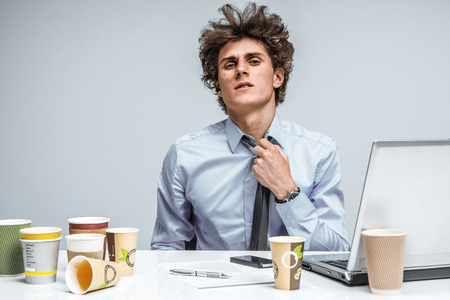 manage clutter: Tired student. Overwhelmed man turned away from the laptop screen. Education concept Stock Photo