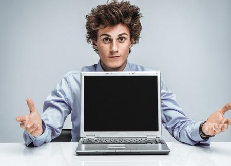 vómito: El encargado joven levantó las manos y en la incredulidad. de negocios moderno en el lugar de trabajo de trabajo con ordenador. Concepto de negocio