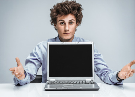 disbelief: Young manager threw up his hands and in disbelief. Modern businessman at the workplace working with computer. Business concept Stock Photo