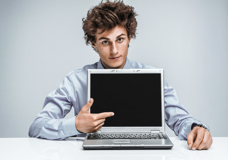 auditors: Young businessman indicates a screen laptop. Modern businessman at the workplace working with computer