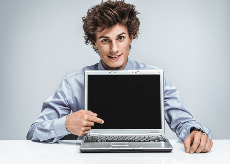 actuary: Smiling businessman at the workplace looking at camera and showing at screen laptop. Business concept
