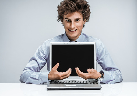 actuary: Friendly young manager shows equal balance of interest, percent. Modern businessman at the workplace working with computer. Business concept
