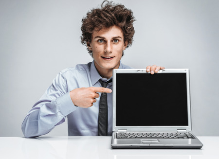 actuary: Young salesman showing at screen laptop  modern businessman at the workplace working with computer
