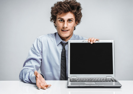 actuary: Young man shows presentation on laptop. Modern businessman at the workplace working with computer. Business concept