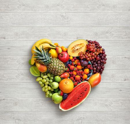 ハートマーク。フルーツ ダイエットのコンセプトです。白い木製のテーブルにさまざまな果物から作られた心の食べ物の写真。高解像度の製品です