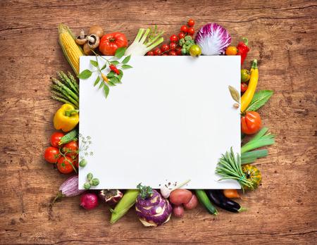 健康食品の背景とコピー スペース。ホワイト ペーパーの古い木製のテーブルで新鮮野菜に囲まれたスタジオ撮影