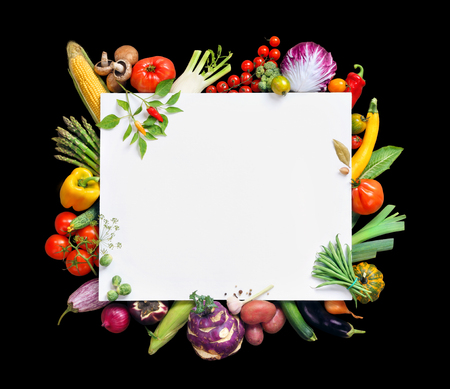photography background: Healthy food background and Copy space. Studio photography of white paper surrounded by fresh vegetables  isolated on black background, top view. High resolution product Stock Photo