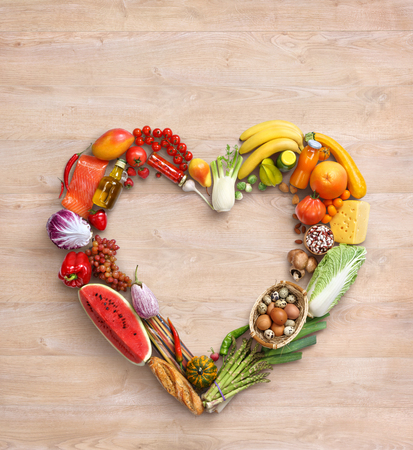 Heart symbol. Healthy eating concept. Food photography of heart made from different vegetables on old wooden table