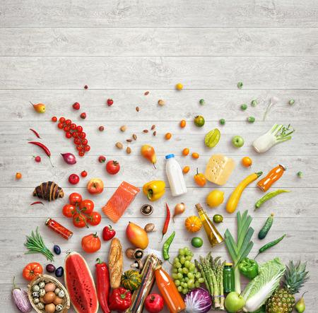Gesunde Lebensmittel Hintergrund. Studio Fotografie von verschiedenen Früchten und Gemüse auf weißem Holz Hintergrund, Ansicht von oben. Hochauflösende Produkt.