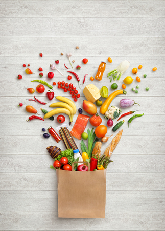 Gezonde voeding in pakket. Studiofotografie van verschillende groenten en fruit op witte houten achtergrond, bovenaanzicht. Hoge resolutie product. Stockfoto