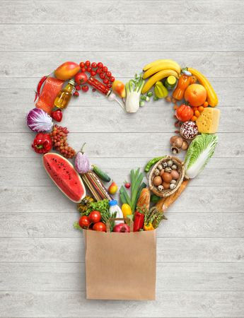 Heart symbol symbol in package. Studio photography of heart made from different fruits and vegetables on white wooden background. Top view. High resolution product.