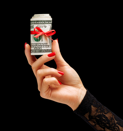 red hand: Womens Hand holding Money with red ribbon isolated on black background. Business concept