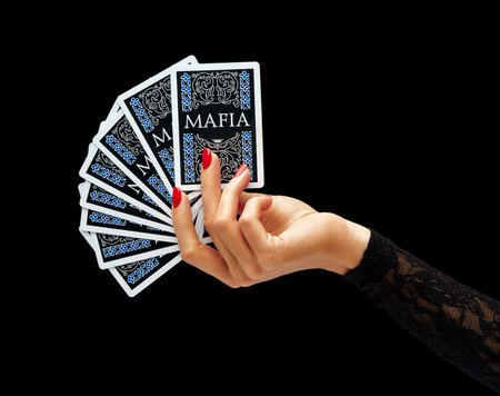 holding close: Womens hand holding playing cards isolated on black background. Business concept Stock Photo