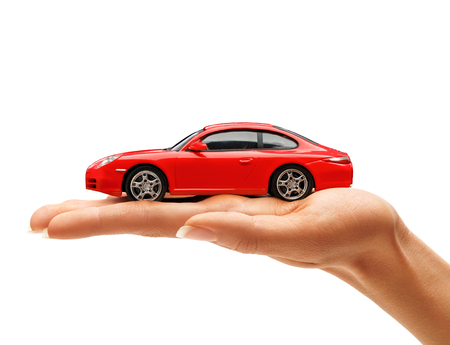 Woman's hand holding a red toy car isolated on white background. Business concept