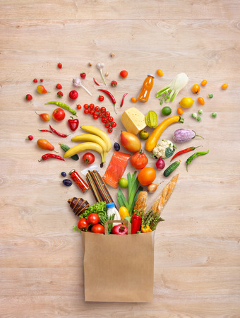 foodstuff: Healthy products in package. Studio photography of different fruits and vegetables on wooden background, top view. High resolution.