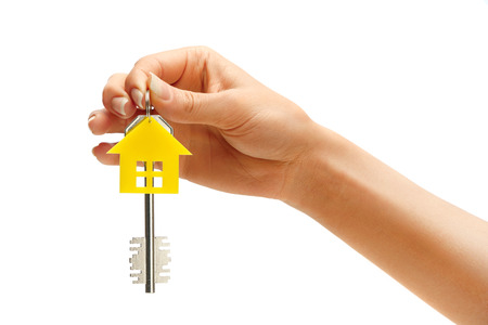 key: Womans hand holding house key with keychain in the form of home isolated on white background Stock Photo