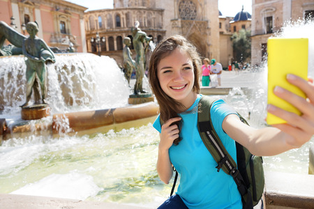 europe travel: Woman tourist taking selfie pictures on Europe travel. Happy candid tourist on Valencia, Spain. Travel and tourism concept.