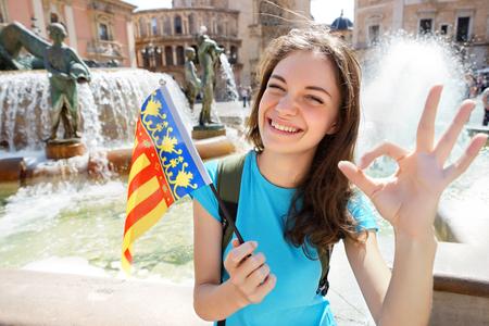 Donna sventolando la bandiera di Valencia felice a Valencia, Spagna. Sorridente ragazza allegra divertirsi di fronte alla Cattedrale.
