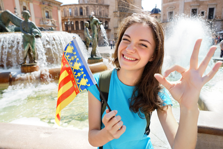 spanish language: Woman waving Valencian flag happy in Valencia, Spain. Smiling cheerful girl having fun in front of Cathedral.