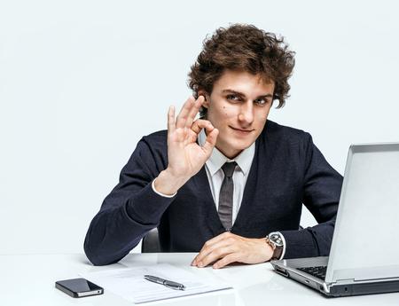 그 좋아을 보여주는 쾌활한 젊은 사업가. 회색 배경에 컴퓨터 작업 직장에서 사업가입니다. 스톡 콘텐츠