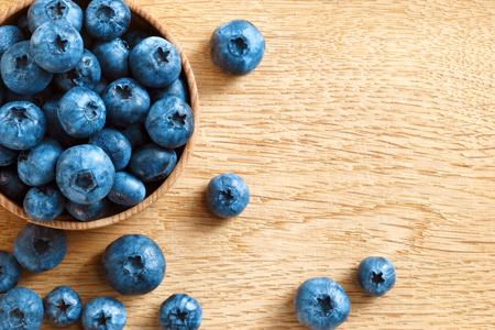 up view: Healthy blueberries in bowl on wooden background. Close up, top view, high resolution product. Harvest Concept