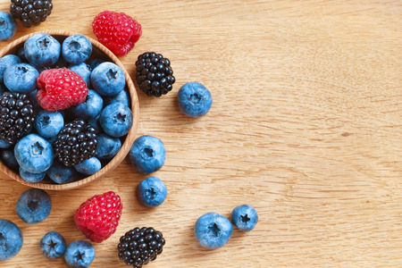 heap up: Heap of sweet tasty berries on wooden table. Close up, top view, high resolution product. Harvest Concept