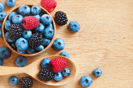 heap up: Heap of tasty berries on wooden table. Close up, top view, high resolution product. Harvest Concept