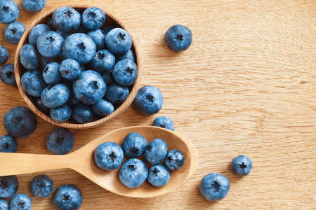 Organic blueberries in bowl on wooden background. Close up, top view, high resolution product. Harvest Concept