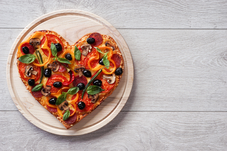 Baked heart-shaped homemade pizza on a cutting board on white wooden background. Close-up Stock Photo