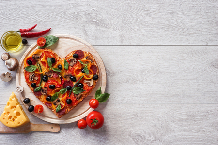 Pizza heart shape with ingredients and copy space on white wooden background. High resolution product.