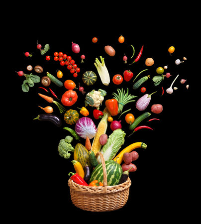 Deluxe food in Basket. Studio photography of different fruits and vegetables isolated on black background. Top view. High resolution product.