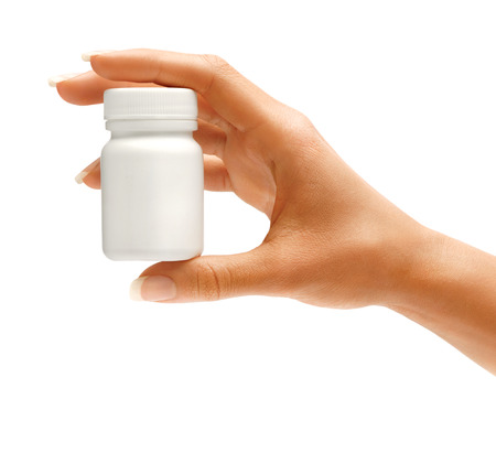 Womans hand holding medical bottle with pills isolated on white background. Close up. High resolution product.
