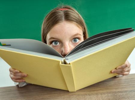 Surpris adolescente avec un livre. Photo de fille de l'école de l'adolescence, concept créatif Retour à l'école