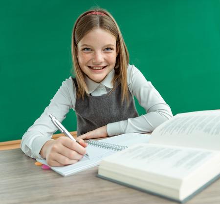 Happy joyful teenage girl teaches homework. Photo of teen school girl, creative concept with Back to school theme