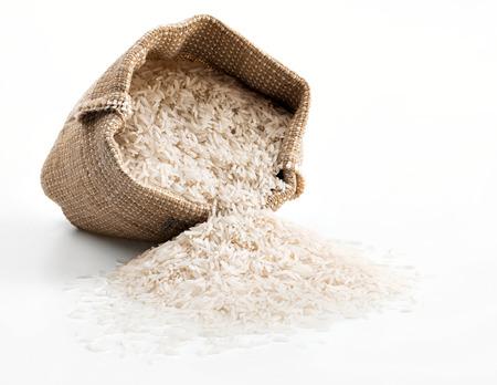 arroz blanco: Saco con arroz dispersos en el fondo blanco. De cerca, producto de alta resolución. Foto de archivo