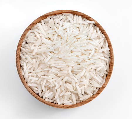 White rice in wooden bowl on white background. Close up, top view, high resolution product. Stock Photo
