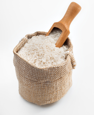 White long rice in a burlap sack and wooden spoon on white background. Close up, high resolution product.