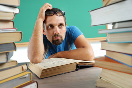 disinterested: Adult teacher at a loss or thinking something. Photo adult man surrounded by books, education concept