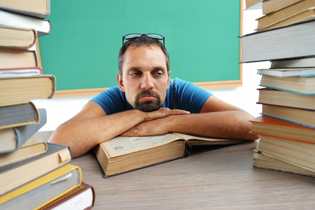 Boredom. Teacher resting his chin on his hands, laying on a table with opened book. Education concept photo