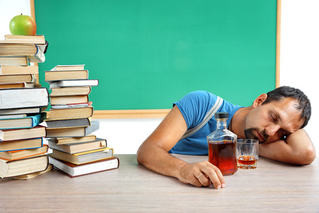 Drunk teacher fall asleep at classroom. Photo of adult man addicted to alcohol at the workplace, education concept photo