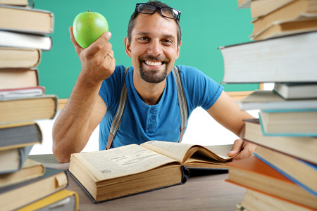Laughing teacher with open book and holding an apple. Photo of adult man wearing glasses, creative concept with Back to school theme photo