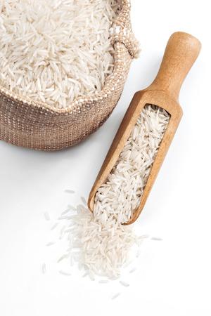 arroz blanco: Arroz en cuchara de madera y saco sobre fondo blanco. De cerca, producto de alta resolución.