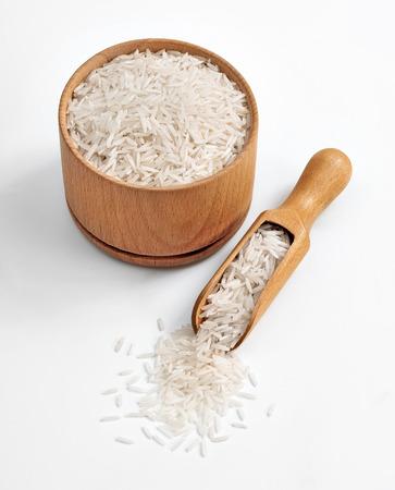 arroz blanco: Arroz en un tazón y cuchara de madera sobre fondo blanco. De cerca, producto de alta resolución. Foto de archivo