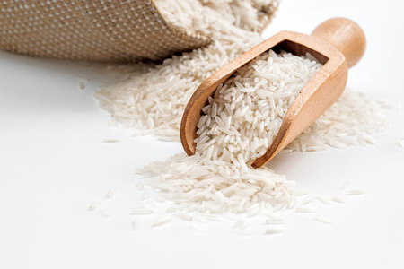 木のスプーンで白い背景の上袋長い米。クローズ アップ