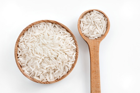 Rice in wooden spoon and bowl on white background.  Top view Stock fotó