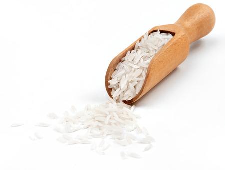 Riso in cucchiaio di legno su sfondo bianco. Avvicinamento