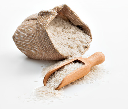 Raw rice in wooden spoon and sack on white background. Close up